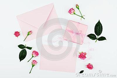 Gift or present box, envelope, paper blank and pink rose flower on white table top view in flat lay style for greeting card.