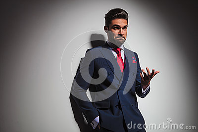 Confused elegant man gesturing and making an undecided stupid fa