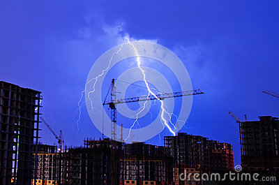 Lightning storm crane weather industrial city building construction night flash