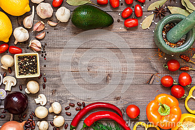 Frame of different fresh organic vegetables and spices on wooden table. Healthy natural food background with copy space.