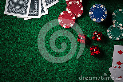Poker chips and gamble cards on casino green table with low key