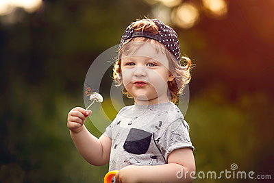 Little boy with dandelion in hand