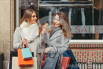 Two girls are happy with a credit card in front of showwindow wi