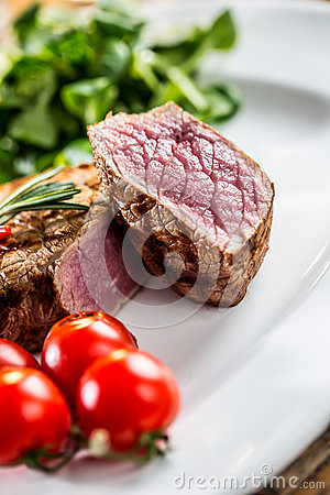 Beef Steak. Juicy beef steak. Gourmet steak with vegetables and glass of rose wine on wooden table