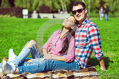 Young loving happy couple in checked shirts, jeans and white sneakers sitting on the green lawn