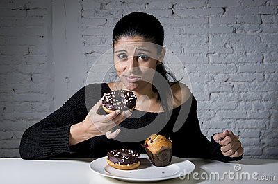 Woman sitting at table feeling guilty forgetting diet eating dish full of junk sugary unhealthy food
