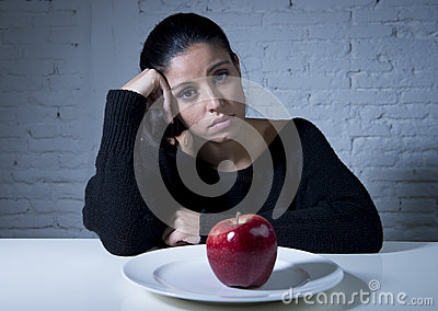 Young woman or teen looking apple fruit on dish as symbol of crazy diet in nutrition disorder