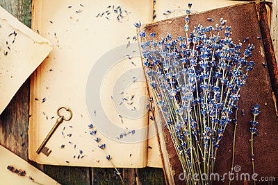 Retro still life with vintage books, key and lavender flowers, nostalgic composition on wooden table top view.