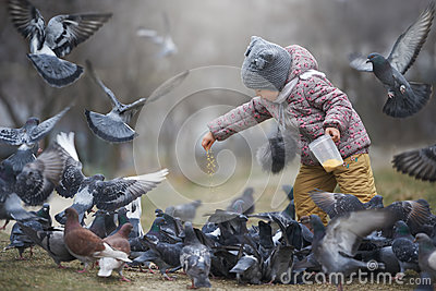 Child feeding a crowd of grey and two brown pigeons