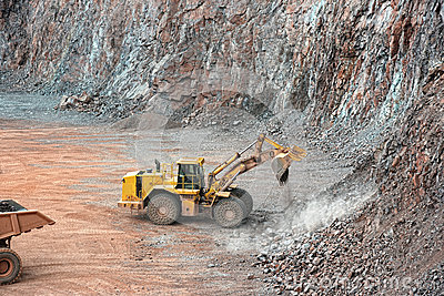 Earthmover in a open pit mine quarry. porphyry rock