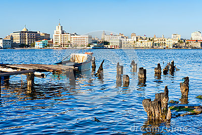 The Old Havana skyline and an old pier with fishing boats on the Bay of Havana