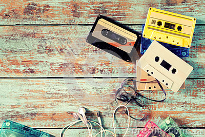 Retro tape cassette with earphone on wood table