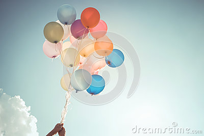 Hands of girl holding multicolored balloons