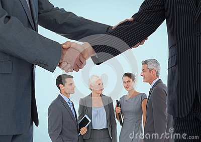 Handshake in front of business people against blue background