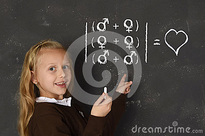 Schoolgirl in uniform holding chalk writing on blackboard standing for freedom of sexuality orientation