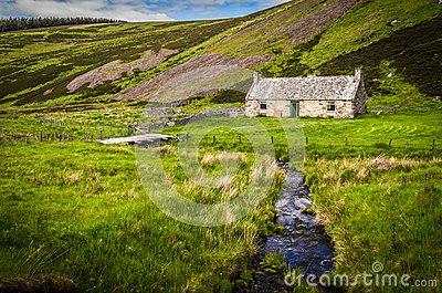 Old abandoned cottage by a rippling stream in Scotland