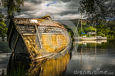 Old abandoned boat on the rippling loch ness lake in Scotland