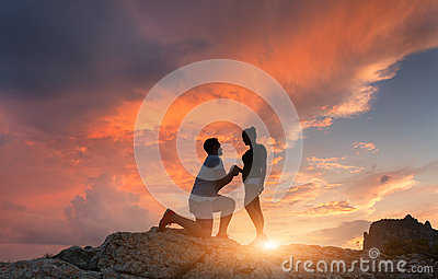 Silhouettes of a man making marriage proposal to his girlfriend
