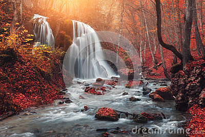 Waterfall at mountain river in autumn forest at sunset