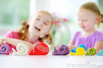Two cute little sisters having fun together with modeling clay at a daycare. Creative kids molding at home. Children play with pla