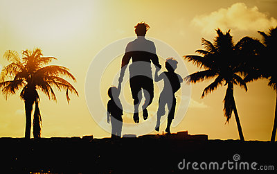 Father with little son and daughter jumping at sunset beach