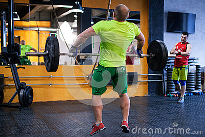 Man performing a barbell snatch at the gym