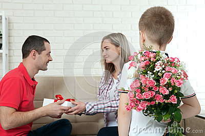 Son hiding bouquet to surprise mommy on mother`s day. Woman, man