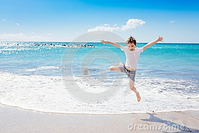 Happy 7 years boy jumping on the beach