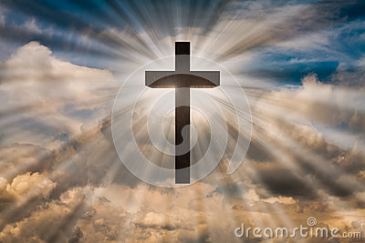 Jesus Christ cross on a sky with dramatic light, clouds, sunbeams. Easter, resurrection, risen Jesus concept