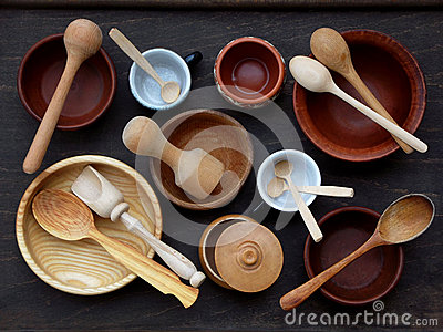 Ceramic, wooden, clay empty handmade bowl, cup and spoon on dark background. Pottery earthenware utensil, kitchenware.