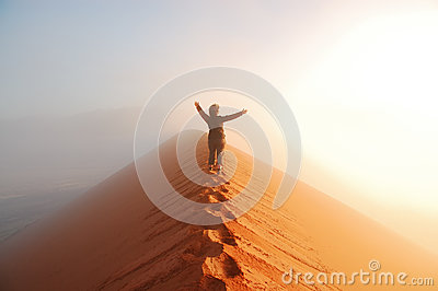 Person standing on top of dune in desert and looking at rising sun in mist with hands up, travel in Africa