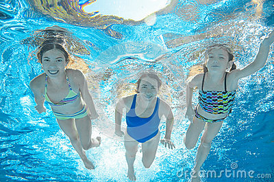Family swims in pool under water, happy active mother and children have fun, fitness and sport with kids on vacation