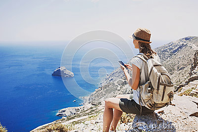 stock image of hiking woman using smart phone taking photo, travel and active lifestyle concept