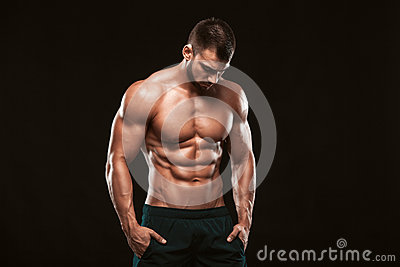 Strong Athletic Man - Fitness Model showing his perfect back isolated on black background with copyspace