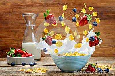 Healthy breakfast with milk, flying corn flakes, strawberries an