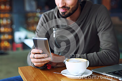 Young handsome cheerful hipster guy at the restaurant using a mobile phone, hands close up. Selective focus.