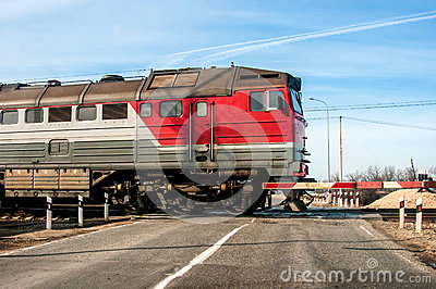 An old russian red train passing across a level crossing, on a small road.