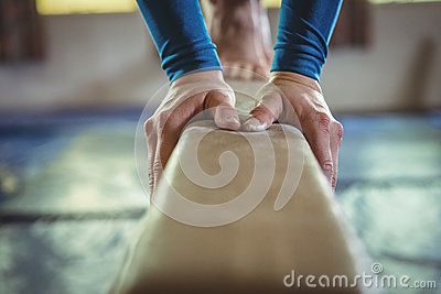 Female gymnast practicing gymnastics on the balance beam
