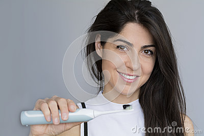 Smiling woman holding toothbrush with black charcoal toothpaste