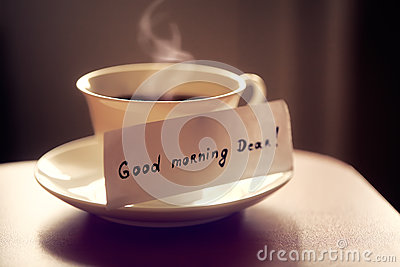 White ceramic cup of tea or coffee with nice letter `good morning dear` on kitchen table. Beautiful photo with breakfast