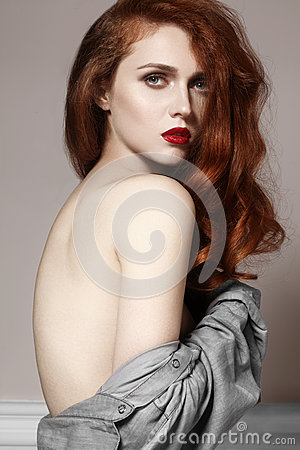 Beautiful ginger young woman with luxury hair style and fashion gloss makeup. Beauty closeup sexy model with red hair