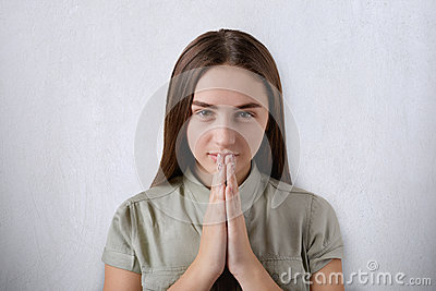 A confident young girl with beautiful dark eyes and hair praying with her hands together on grey background having believe in bett