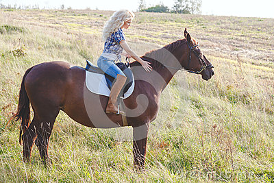 Portrait of young beautiful blond hair woman riding horse. Travel with animal