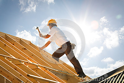 Roofer carpenter working on roof on construction site