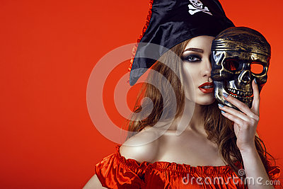 Portrait of gorgeous sexy woman with provocative make-up in pirate costume hiding the half of her face behind skull mask