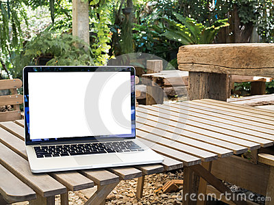 Wood table with blank screen on laptop at parkland.