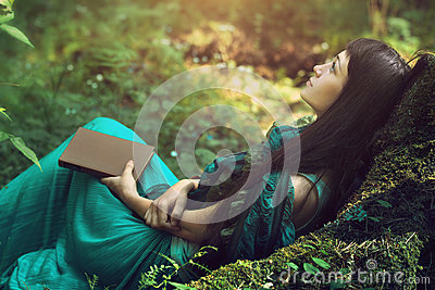 Mysterious image of a beautiful woman in woods. Lonely mysterious girl on background of wild nature. Woman in search of herself