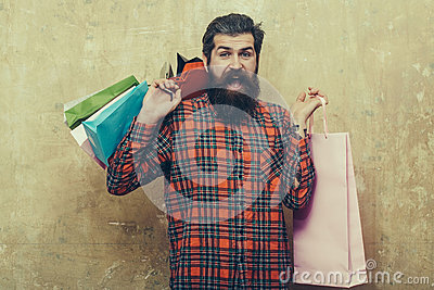 Happy bearded man holding colorful paper shopping bags