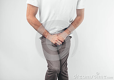 A man holding his penis with on the white background. Wants to go to the toilet.