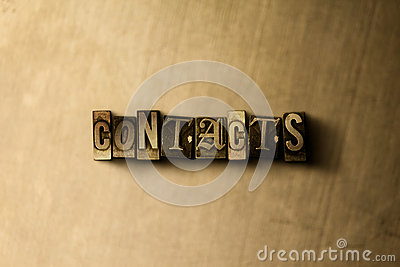 CONTACTS - close-up of grungy vintage typeset word on metal backdrop
